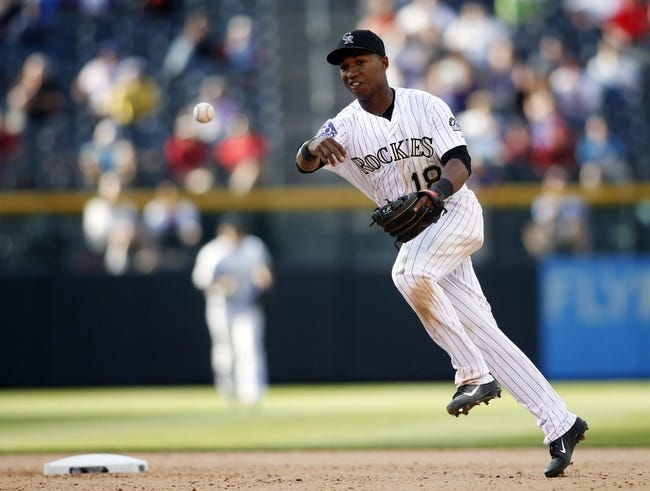 Sep 19, 2013; Denver, CO, USA; Colorado Rockies second baseman Jonathan Herrera (18) fields a ground ball during the tenth inning against the St. Louis Cardinals at Coors Field. The Rockies won 7-6 in 15 innings.  Mandatory Credit: Chris Humphreys-USA TODAY Sports