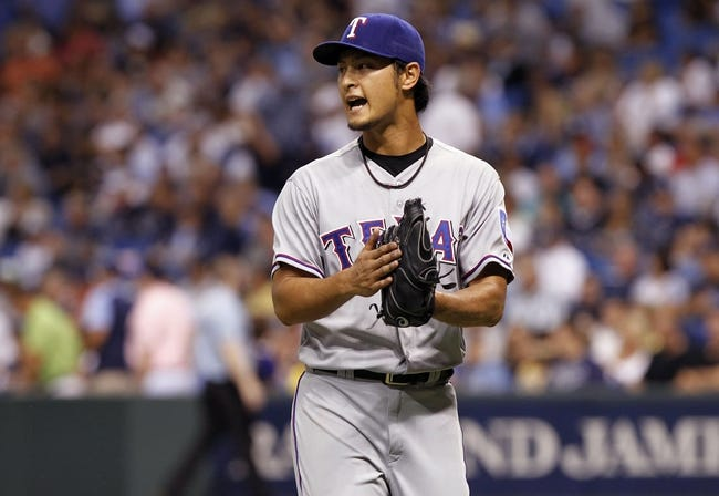 Sep 19, 2013; St. Petersburg, FL, USA; Texas Rangers starting pitcher Yu Darvish (11) reacts after he pitched the third inning against the Tampa Bay Rays at Tropicana Field. Mandatory Credit: Kim Klement-USA TODAY Sports