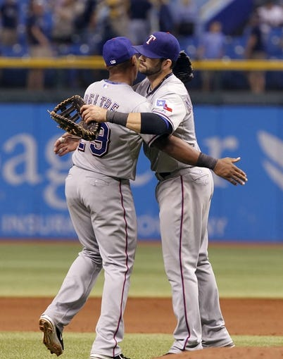 Sep 19, 2013; St. Petersburg, FL, USA; Texas Rangers third baseman Adrian Beltre (29) and first baseman Mitch Moreland (18) hug after they beat the Tampa Bay Rays at Tropicana Field. Texas Rangers defeated the Tampa Bay Rays 8-2. Mandatory Credit: Kim Klement-USA TODAY Sports
