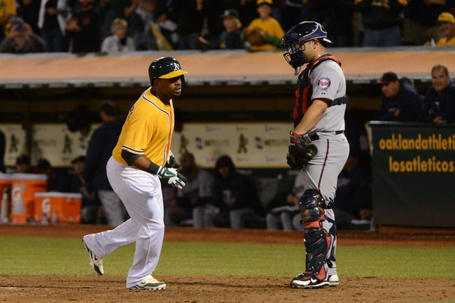 September 19, 2013; Oakland, CA, USA; Oakland Athletics second baseman Alberto Callaspo (18, left) crosses home plate after hitting a solo home run against Minnesota Twins catcher Josmil Pinto (43) during the sixth inning at O.co Coliseum. Mandatory Credit: Kyle Terada-USA TODAY Sports