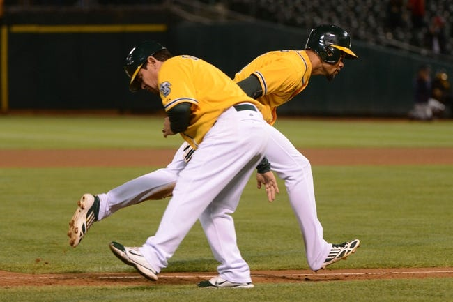 September 19, 2013; Oakland, CA, USA; Oakland Athletics center fielder Coco Crisp (4, right) is congratulated by third base coach Mike Gallego (2, left) for hitting a two-run home run against the Minnesota Twins during the eighth inning at O.co Coliseum. The Athletics defeated the Twins 8-6. Mandatory Credit: Kyle Terada-USA TODAY Sports