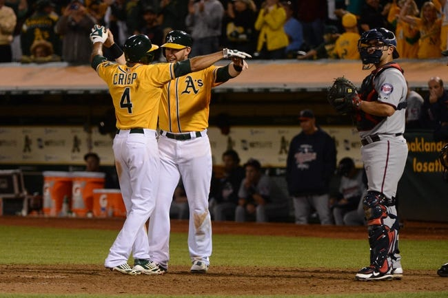 September 19, 2013; Oakland, CA, USA; Oakland Athletics center fielder Coco Crisp (4) is congratulated by first baseman Daric Barton (10, center) for hitting a two-run home run as Minnesota Twins catcher Josmil Pinto (43, right) looks on during the eighth inning at O.co Coliseum. The Athletics defeated the Twins 8-6. Mandatory Credit: Kyle Terada-USA TODAY Sports