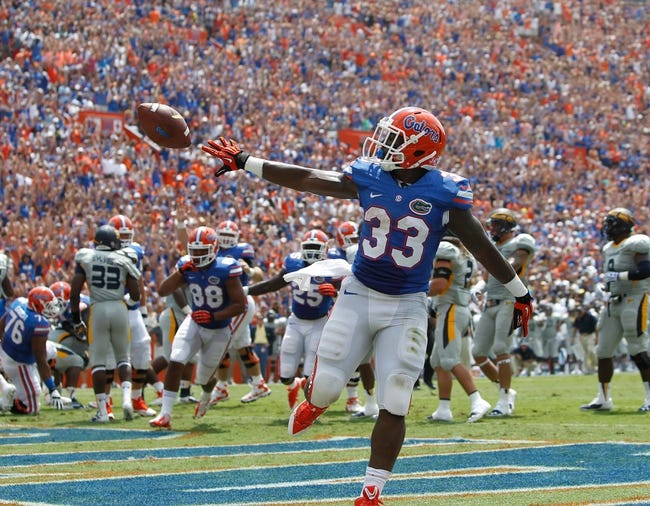Aug 31, 2013; Gainesville, FL, USA; Florida Gators running back Mack Brown (33) throws the ball after he ran it in for a touchdown during the first quarter against the Toledo Rockets at Ben Hill Griffin Stadium. Mandatory Credit: Kim Klement-USA TODAY Sports