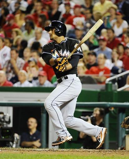 Sep 20, 2013; Washington, DC, USA; Miami Marlins second baseman Donovan Solano (17) hits a single during the sixth inning against the Washington Nationals at Nationals Park. Mandatory Credit: Brad Mills-USA TODAY Sports