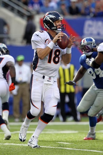 Sep 15, 2013; East Rutherford, NJ, USA; Denver Broncos quarterback Peyton Manning (18) drops back to pass against the New York Giants at MetLife Stadium. Mandatory Credit: Brad Penner-USA TODAY Sports