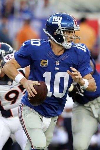 Sep 15, 2013; East Rutherford, NJ, USA; New York Giants quarterback Eli Manning (10) scrambles with the ball against the Denver Broncos at MetLife Stadium. Mandatory Credit: Brad Penner-USA TODAY Sports