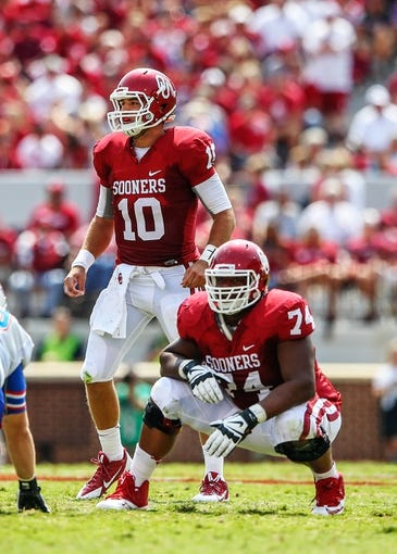 Sep 14, 2013; Norman, OK, USA; Oklahoma Sooners quarterback Blake Bell (10) and offensive linesman Adam Shead (74) look to the sidelines for a play during the game against the Tulsa Golden Hurricane at Gaylord Family - Oklahoma Memorial Stadium. Oklahoma won 51-20. Mandatory Credit: Kevin Jairaj-USA TODAY Sports