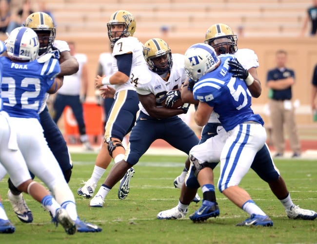 Sep 21, 2013; Durham, NC, USA;  Pitt Panthers running back Isaac Bennett (34) caries the ball as Duke Blue Devils  linebacker Kelby Brown (59) defends during the first half at Wallace Wade Stadium. Mandatory Credit: Rob Kinnan-USA TODAY Sports