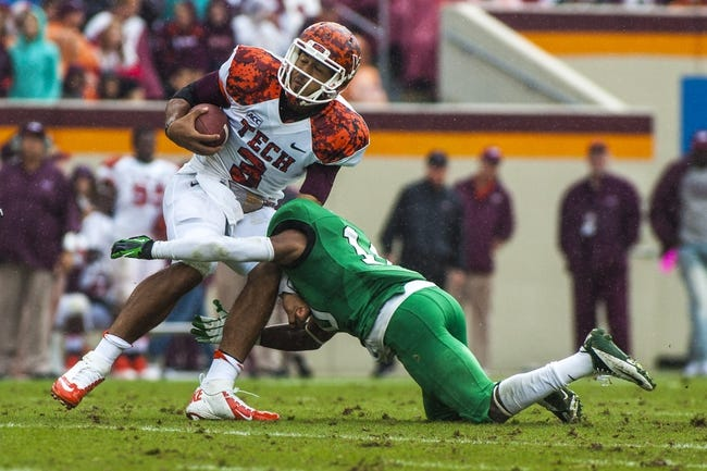 Sep 21, 2013; Blacksburg, VA, USA; Virginia Tech Hokies quarterback Logan Thomas (3) is tackled by Marshall Thundering Herd defensive back Corey Tindal (10) during the first half at Lane Stadium. Mandatory Credit: Peter Casey-USA TODAY Sports