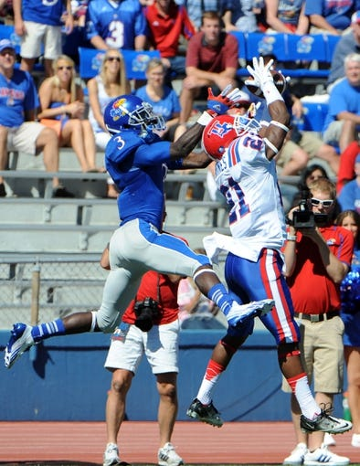 Sep 21, 2013; Lawrence, KS, USA; Louisiana Tech Bulldogs defensive back Adairius Barnes (21) lands out of bounds after catching a pass intended for Kansas Jayhawks running back Tony Pierson (3) in the first half at Memorial Stadium. Mandatory Credit: John Rieger-USA TODAY Sports