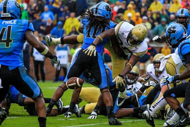 Sep 21, 2013; Atlanta, GA, USA; Georgia Tech Yellow Jackets running back David Sims (20) turns the ball over in the end zone after being hit by North Carolina Tar Heels safety Tre Boston (10) in the first half at Bobby Dodd Stadium. The play was ruled a touchdown. Mandatory Credit: Daniel Shirey-USA TODAY Sports