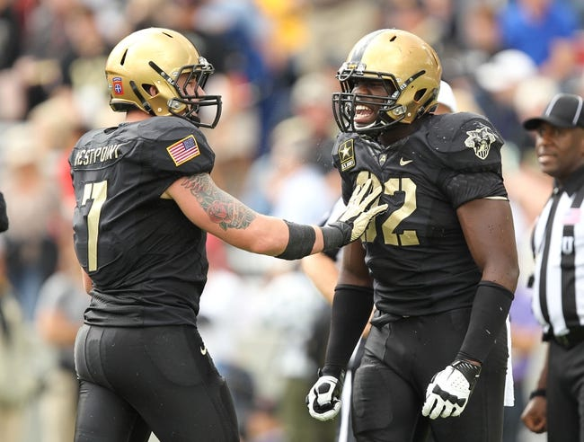 Sep 21, 2013; West Point, NY, USA; Army Black Knights defensive lineman Mike Ugenyi (92) is restrained by linebacker Dalton Mendenhall (7) during the second half at Michie Stadium. Mandatory Credit: Danny Wild-USA TODAY Sports