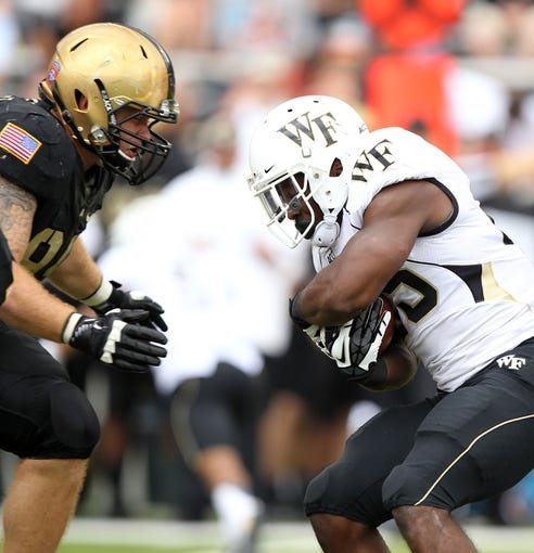 Sep 21, 2013; West Point, NY, USA;  Wake Forest Demon Deacons running back Josh Harris (25) carries the ball as Army Black Knights defensive end Robert Kough (99) looks to make the tackle at Michie Stadium. Mandatory Credit: Danny Wild-USA TODAY Sports