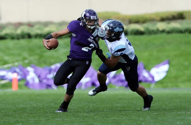 Sep 21, 2013; Evanston, IL, USA; Northwestern Wildcats quarterback Kain Colter (2) is tackled by Maine Black Bears defensive back Troy Eastman (6) during the first quarter at Ryan Field.  Mandatory Credit: Jerry Lai-USA TODAY Sports