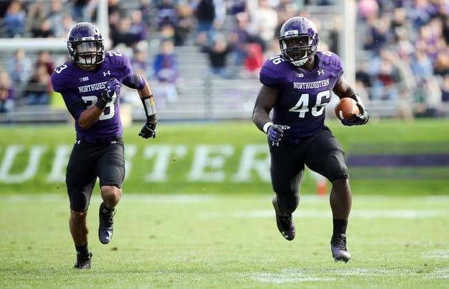Sep 21, 2013; Evanston, IL, USA; Northwestern Wildcats linebacker Damien Proby (46) returns an interception for a touchdown while escorted by cornerback Nick VanHoose (23) during the second quarter against the Maine Black Bears at Ryan Field.  Mandatory Credit: Jerry Lai-USA TODAY Sports