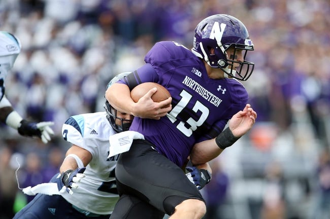 Sep 21, 2013; Evanston, IL, USA; Northwestern Wildcats quarterback Trevor Siemian (13) is tackled by Maine Black Bears defensive back Cabrinni Goncalves (2) during the second quarter at Ryan Field.  Mandatory Credit: Jerry Lai-USA TODAY Sports