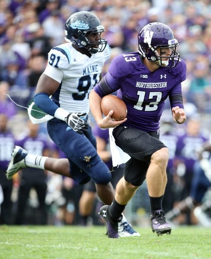 Sep 21, 2013; Evanston, IL, USA; Northwestern Wildcats quarterback Trevor Siemian (13) runs away from Maine Black Bears defensive lineman Jonathan Lewis (91) during the second quarter at Ryan Field.  Mandatory Credit: Jerry Lai-USA TODAY Sports