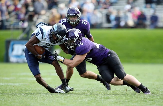 Sep 21, 2013; Evanston, IL, USA; Maine Black Bears wide receiver Derrick Johnson (8) is tackled by Northwestern Wildcats linebacker Collin Ellis (45) and cornerback Nick VanHoose (23)  during the second quarter at Ryan Field.  Mandatory Credit: Jerry Lai-USA TODAY Sports