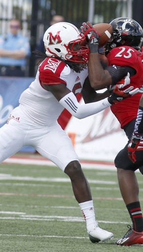 Sep 21, 2013; Oxford, OH, USA; Cincinnati Bearcats safety Arryn Chenault (25) intercepts a pass against Miami (Oh) Redhawks wide receiver Rokeem Williams (6) during the first quarter at Fred Yager Stadium. Mandatory Credit: David Kohl-USA TODAY Sports