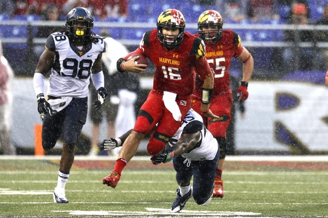 Sep 21, 2013; Baltimore, MD, USA; Maryland Terrapins quarterback CJ Brown (16) runs for a gain past diving West Virginia Mountaineers lineman Eric Kinsey (45) at M&T Bank Stadium. Mandatory Credit: Mitch Stringer-USA TODAY Sports