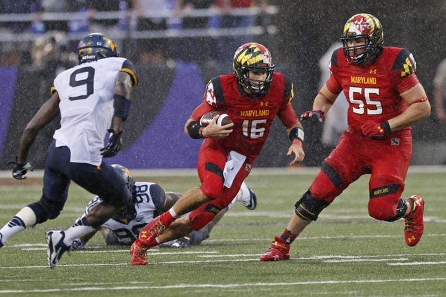 Sep 21, 2013; Baltimore, MD, USA; Maryland Terrapins quarterback CJ Brown (16) runs for a gain past West Virginia Mountaineers safety KJ Dillon (9) with blocking from lineman Ryan Doyle (55) at M&T Bank Stadium. Mandatory Credit: Mitch Stringer-USA TODAY Sports