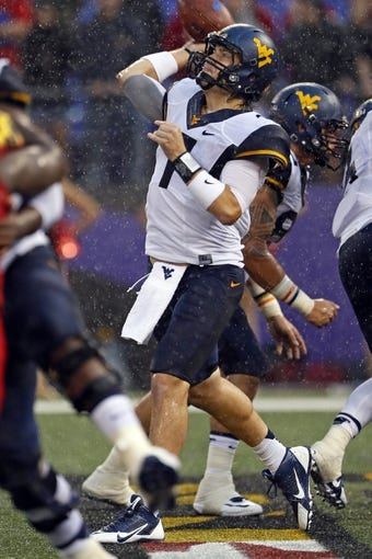 Sep 21, 2013; Baltimore, MD, USA; West Virginia Mountaineers quarterback Ford Childress (7) throws an incomplete pass under pressure against the Maryland Terrapins at M&T Bank Stadium. Mandatory Credit: Mitch Stringer-USA TODAY Sports