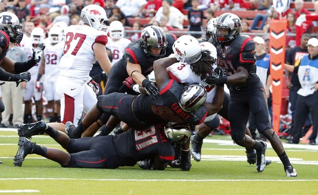 Sep 21, 2013; Piscataway, NJ, USA;  Rutgers Scarlet Knights defenders tackle Arkansas Razorbacks running back Alex Collins (3) during the second half at High Points Solutions Stadium. Rutgers won 28-24. Mandatory Credit: Jim O'Connor-USA TODAY Sports