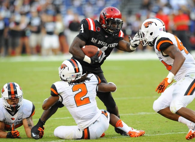 Sep 21, 2013; San Diego, CA, USA; San Diego State Aztecs running back Adam Muema (4) is tackled by Oregon State Beavers cornerback Steven Nelson (2) after a short gain during the first half at Qualcomm Stadium. Mandatory Credit: Christopher Hanewinckel-USA TODAY Sports