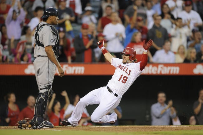 Sep 21, 2013; Anaheim, CA, USA; Los Angeles Angels left fielder Collin Cowgill (19) slides in for a score off of a three RBI double hit by Los Angeles Angels second baseman Grant Green (not pictured) against the Seattle Mariners during the second inning at Angel Stadium of Anaheim. Mandatory Credit: Kelvin Kuo-USA TODAY Sports