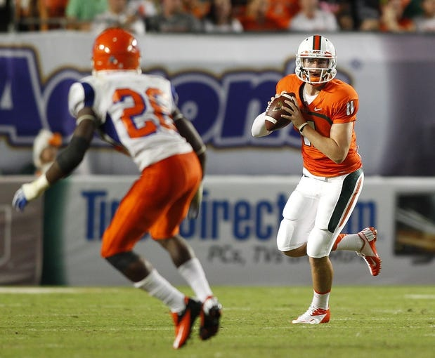 Sep 21, 2013; Miami Gardens, FL, USA; Miami Hurricanes quarterback Ryan Williams (11) rolls out to pass as Savannah State Tigers defensive back Gregory Brown (26) defends in the second quarter at Sun Life Stadium. Mandatory Credit: Robert Mayer-USA TODAY Sports