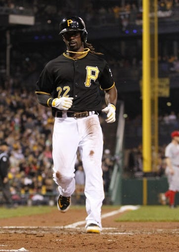 Sep 21, 2013; Pittsburgh, PA, USA; Pittsburgh Pirates center fielder Andrew McCutchen (22) scores on a sacrifice fly against the Cincinnati Reds during the sixth inning at PNC Park. The Pittsburgh Pirates won 4-2. Mandatory Credit: Charles LeClaire-USA TODAY Sports