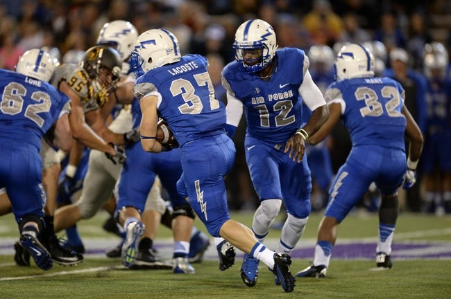 Sep 21, 2013; Colorado Springs, CO, USA; Air Force Falcons quarterback Jaleel Awini (12) hands off to running back Anthony LaCoste (37) against the Wyoming Cowboys in the first quarter at Falcon Stadium. Mandatory Credit: Ron Chenoy-USA TODAY Sports