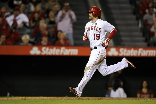 Sep 21, 2013; Anaheim, CA, USA; Los Angeles Angels left fielder Collin Cowgill (19) scores a run after a wild pitch by Seattle Mariners pitcher Joe Saunders (not pictured) during the seventh inning at Angel Stadium of Anaheim. Mandatory Credit: Kelvin Kuo-USA TODAY Sports