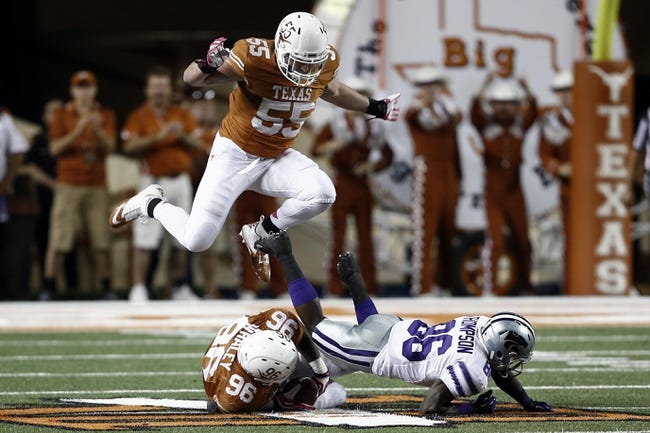 Sep 21, 2013; Austin, TX, USA; Texas Longhorns linebacker Dalton Santos (55) leaps over defensive tackle Chris Whaley (96) after Whaley recovers the fumble as Kansas State Wildcats wide receiver Tramaine Thompson (86) scrambles for the ball during the fourth quarter of a football game at Darrell K Royal-Texas Memorial Stadium. The Longhorns won 31-21. Mandatory Credit: Jim Cowsert-USA TODAY Sports