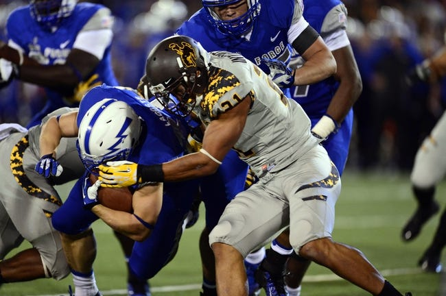 Sep 21, 2013; Colorado Springs, CO, USA; Air Force Falcons running back Anthony LaCoste (37) is tackled by Wyoming Cowboys linebacker Mark Nzeocha (21) in the second quarter at Falcon Stadium. Mandatory Credit: Ron Chenoy-USA TODAY Sports