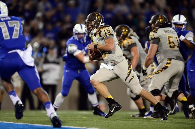 Sep 21, 2013; Colorado Springs, CO, USA; Wyoming Cowboys quarterback Brett Smith (16) runs for a six yard touchdown against the Air Force Falcons in the second quarter at Falcon Stadium. Mandatory Credit: Ron Chenoy-USA TODAY Sports