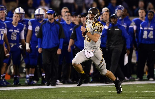 Sep 21, 2013; Colorado Springs, CO, USA; Wyoming Cowboys quarterback Brett Smith (16) runs for a gain against the Air Force Falcons in the second quarter at Falcon Stadium. Mandatory Credit: Ron Chenoy-USA TODAY Sports