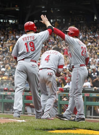 Sep 22, 2013; Pittsburgh, PA, USA; Cincinnati Reds first baseman Joey Votto (19) and second baseman Brandon Phillips (4) and left fielder Chris Heisey (28) react after all three players scored on a double by right fielder Jay Bruce (not pictured) against the Pittsburgh Pirates during the first inning at PNC Park. Mandatory Credit: Charles LeClaire-USA TODAY Sports