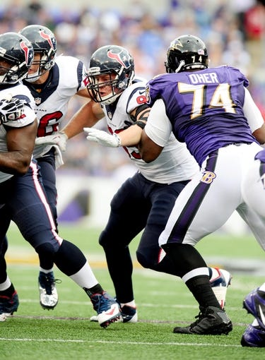 Sep 22, 2013; Baltimore, MD, USA; Houston Texans defensive end J.J. Watt (99) rushes the quarterback against Baltimore Ravens offensive tackle Michael Oher (74) at M&T Bank Stadium. Mandatory Credit: Evan Habeeb-USA TODAY Sports