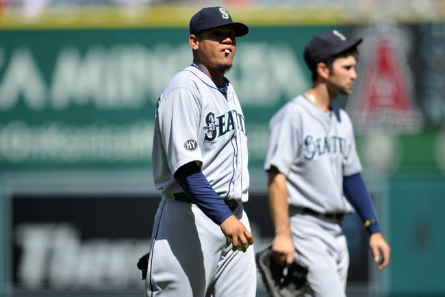 September 22, 2013; Anaheim, CA, USA; Seattle Mariners starting pitcher Felix Hernandez (34) walks to the dugout during a stoppage in play in the third inning at Angel Stadium of Anaheim. The stoppage occurred due to bees on the playing field. Mandatory Credit: Gary A. Vasquez-USA TODAY Sports