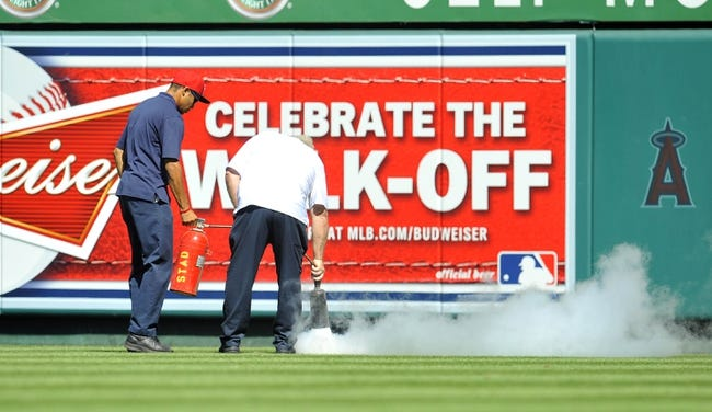 September 22, 2013; Anaheim, CA, USA; Los Angeles Angels stadium workers use an extinguisher to disperse a swarm of bees during the fourth inning at Angel Stadium of Anaheim. Mandatory Credit: Gary A. Vasquez-USA TODAY Sports