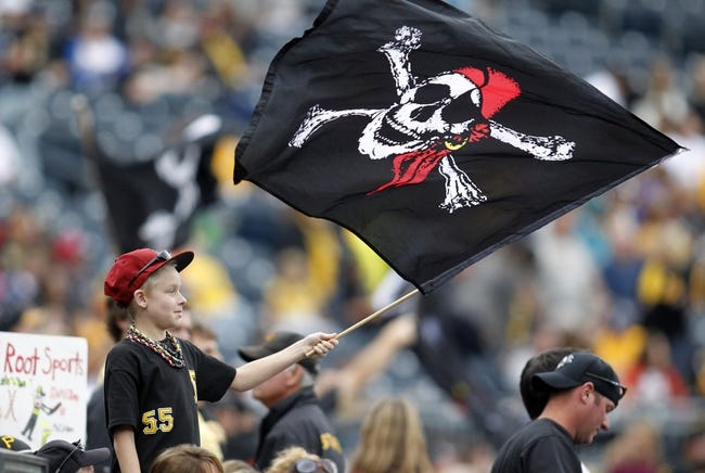 Sep 22, 2013; Pittsburgh, PA, USA; A Pittsburgh Pirates fan waves a jolly roger flag against the Cincinnati Reds during the ninth inning at PNC Park.The Reds won 11-3.  Mandatory Credit: Charles LeClaire-USA TODAY Sports
