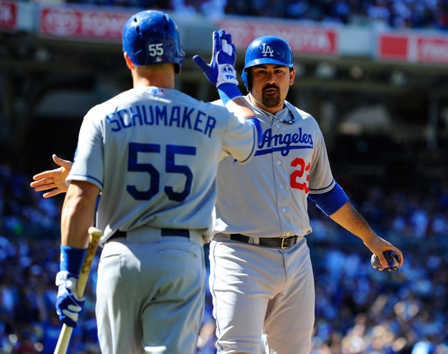 Sep 22, 2013; San Diego, CA, USA; Los Angeles Dodgers first baseman Adrian Gonzalez (23) is congratulated by second baseman Skip Shumaker (55) after scoring on a triple by third baseman Michael Young (not pictured) during the seventh inning against the San Diego Padres at Petco Park. Mandatory Credit: Christopher Hanewinckel-USA TODAY Sports