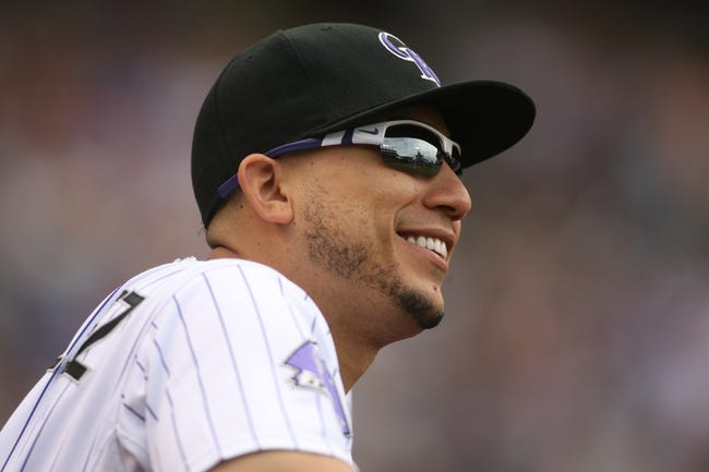 Sep 22, 2013; Denver, CO, USA; Colorado Rockies left fielder Carlos Gonzalez (5) watches from the dugout during the third inning against the Arizona Diamondbacks at Coors Field. Mandatory Credit: Chris Humphreys-USA TODAY Sports