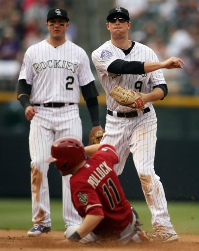 Sep 22, 2013; Denver, CO, USA; Colorado Rockies second baseman DJ LeMahieu (9) turns a double play during the fourth inning against the Arizona Diamondbacks at Coors Field. Mandatory Credit: Chris Humphreys-USA TODAY Sports