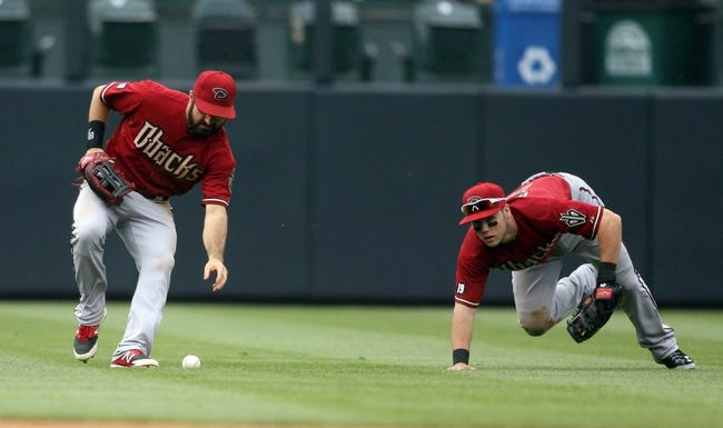 Sep 22, 2013; Denver, CO, USA; Arizona Diamondback shortstop Chris Owings (right) and left fielder Adam Eaton (6) chase after a fly ball during the fourth inning against the Colorado Rockies at Coors Field. Mandatory Credit: Chris Humphreys-USA TODAY Sports