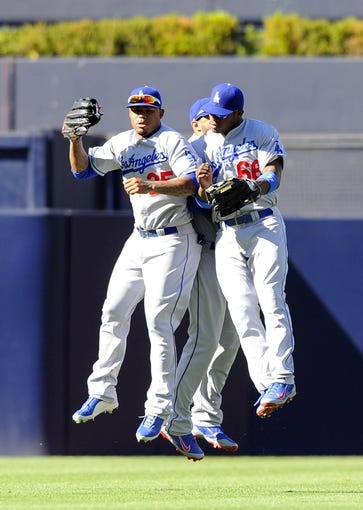 Sep 22, 2013; San Diego, CA, USA; Los Angeles Dodgers left fielder Carl Crawford (left), center fielder Matt Kemp (back) and right fielder Yasiel Puig (66) celebrate after a 1-0 win against the San Diego Padres at Petco Park. Mandatory Credit: Christopher Hanewinckel-USA TODAY Sports