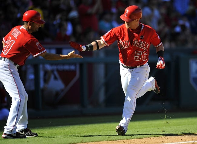 September 22, 2013; Anaheim, CA, USA; Los Angeles Angels right fielder Kole Calhoun (56) is congratulated by third base coach Dino Ebel (21) after he hits a solo home run during the eighth inning against the Seattle Mariners at Angel Stadium of Anaheim. Mandatory Credit: Gary A. Vasquez-USA TODAY Sports
