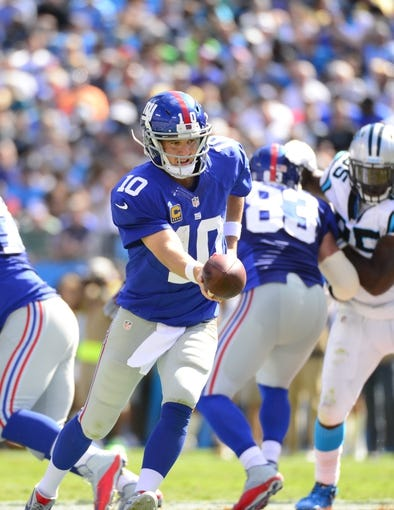 Sep 22, 2013; Charlotte, NC, USA; New York Giants quarterback Eli Manning (10) with the ball in the third quarter. The Carolina Panthers defeated the New York Giants 38-0 at Bank of America Stadium. Mandatory Credit: Bob Donnan-USA TODAY Sports