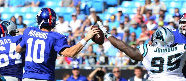 Sep 22, 2013; Charlotte, NC, USA; New York Giants quarterback Eli Manning (10) looks to pass as Carolina Panthers defensive end Charles Johnson (95) pressures in the fourth quarter. The Carolina Panthers defeated the New York Giants 38-0 at Bank of America Stadium. Mandatory Credit: Bob Donnan-USA TODAY Sports